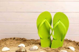 Flip-Flops im Sand mit Muscheln